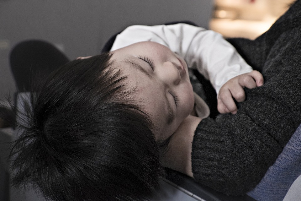 Toddler asleep in adult's arms