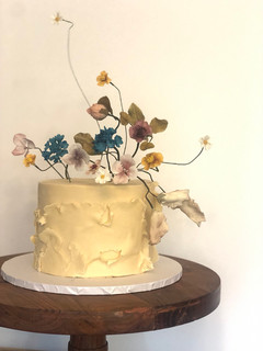 Single tier celebration cake with ruffles and sugar flowers