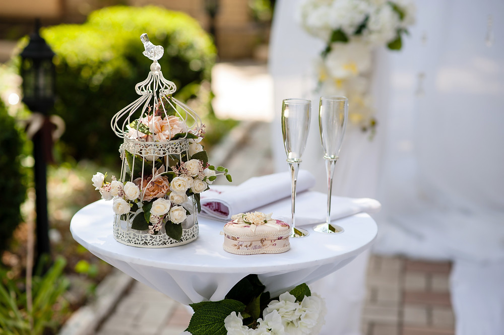 fancy small bird cage with roses inside with a heart box and two champagne glasses on a tray