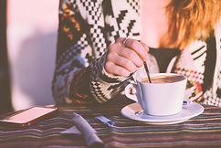 Girl stirring a coffee cup