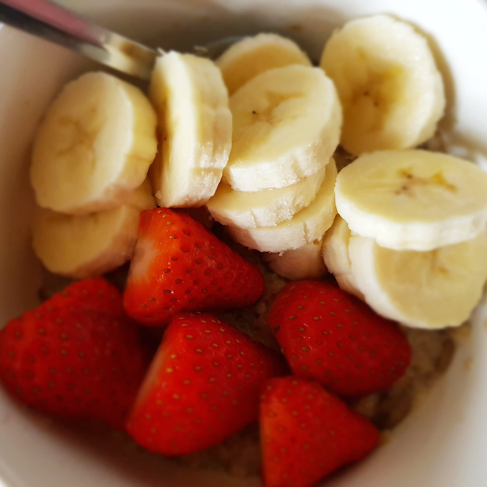 Porridge topped with sliced strawberries and banana