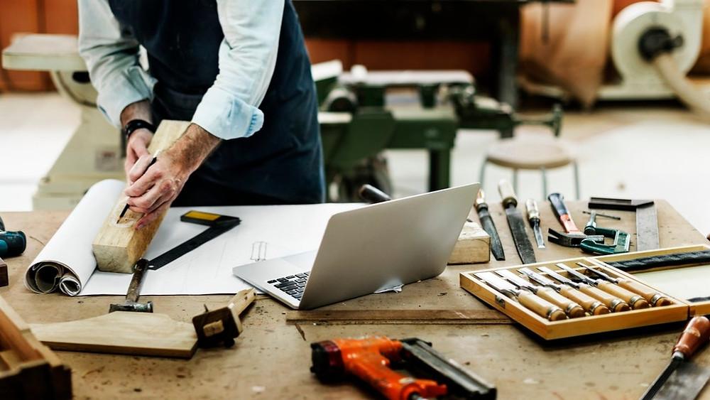 Der PC neben Säge und Winkelmesser als Werkzeug in der Tischlerei