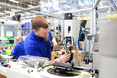 operator assembles machine in a factory
