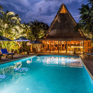 Kaya Bloom Ecolodge at night by the pool.