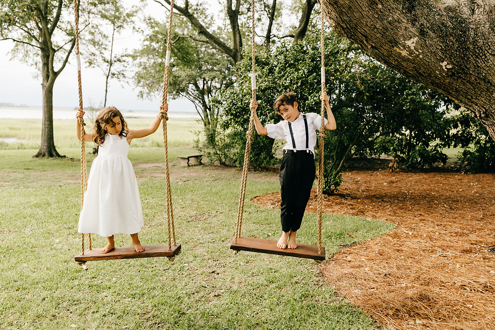 Rustic, wooden swings hanging from a tree for an outdoor wedding reception at Lowndes Grove in Charleston, South Carolina