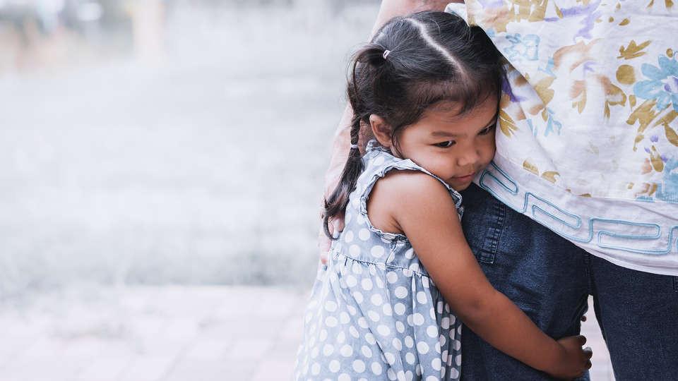 Child clinging to leg