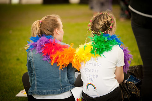 Glos Pride - 2 People Sitting with rainbow feather boa.