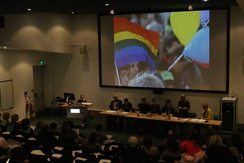 UoG Lecture Theatre with Rainbow flag on projector screen.