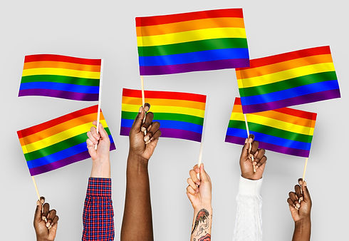 Hands of different skin tones holding rainbow flags.
