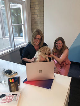 Two teachers smiling as they look into a laptop holding a dog
