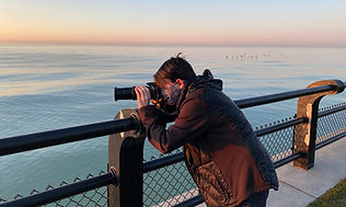 A boy with a telescope looking out to sea