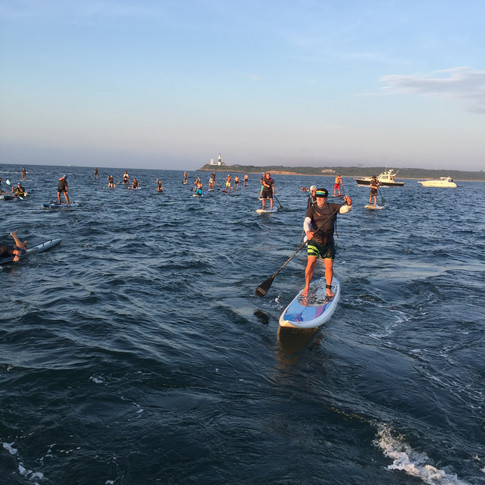 Paddlers with lighthouse in the distance.JPG