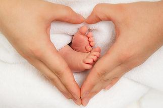 Pieds_bébé_dans_mains_coeur.jpg