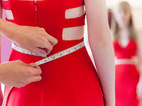 lady in a red dress getting measured with a measuring tape