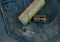 pocket of blue jeans with spool of thread, needle and thimble laying on top