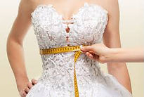 white wedding dress being measured at waist with a yellow measuring tape
