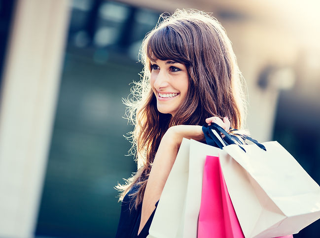 Happy woman holding shopping bags and sm