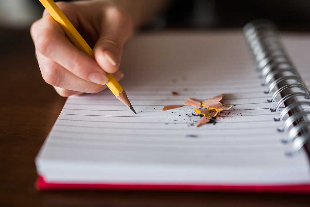 A hand grips a pencil, poised on a sheet of lined paper, next to a pile of pencil shavings.