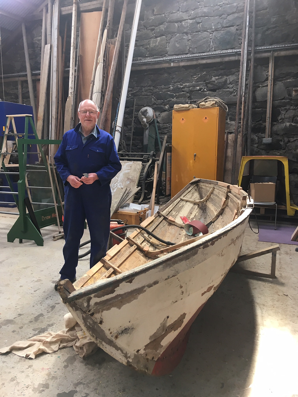 Martin Randall standing next to the hybrid færing in the Shetland Museum boat shed. Photograph taken by Moder Dy June 2019.