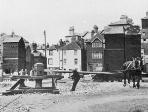 A horse-drawn capstan used to haul the boats up the steep shingle beach. Note the net drying sheds in the background. Photograph: ©The Mariner's Mirror (Hornell, 1938: 213)