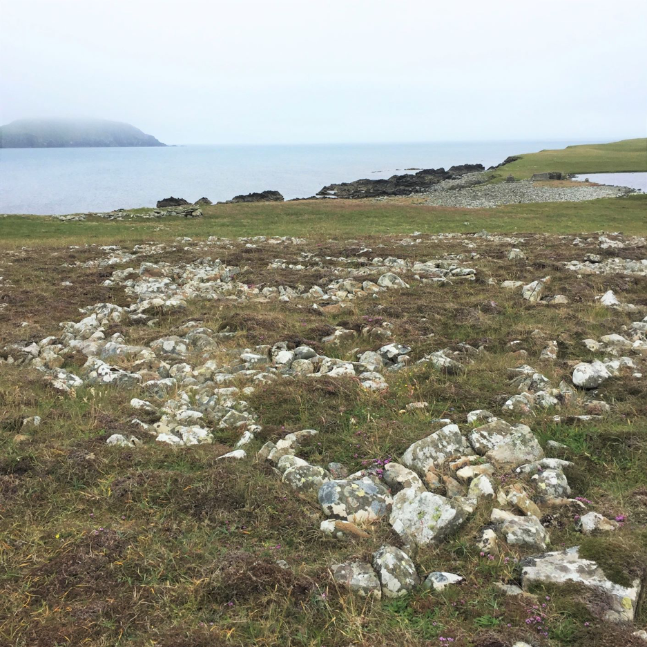 In the foreground there are large rounded pebbles that have been used to create an artificial fish drying beach. Upper left in the photo boat noosts can be seen. The natural drying beach lies to the right. Fob bound Sumburgh Head can be seen in the distance.