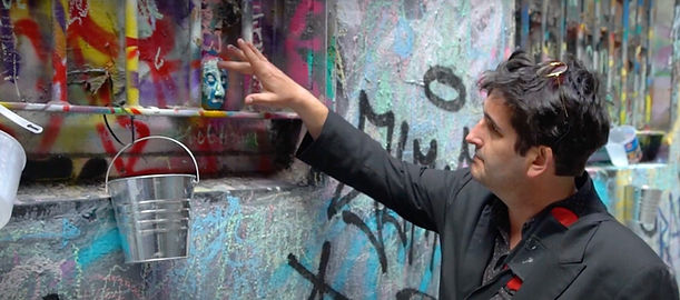 Adrian Doyle points out street sculpture on colourful graffiti covered wall in Melbourne laneway