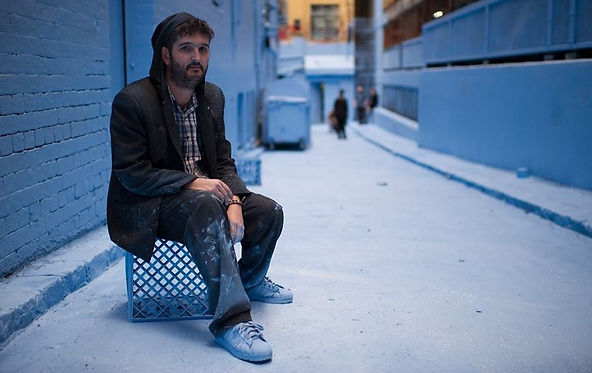 Adrian Doyle sits on a blue milk crate in a Melbourne laneway covered completely in baby blue paint