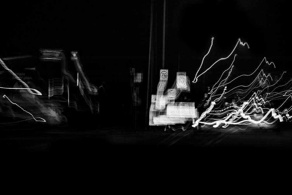 Black and white long exposure photograph taken at night with light trails and blurred subjects. Photography by Megan Kennedy