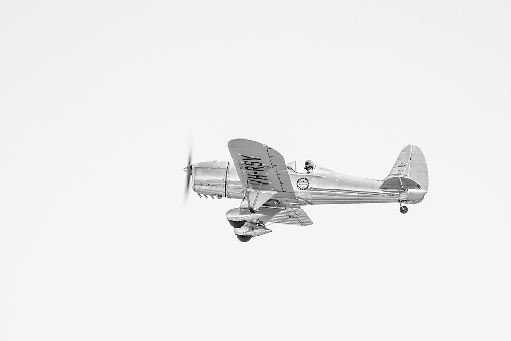 An airborne Ryan STM S2 in black and white photographed by Megan Kennedy
