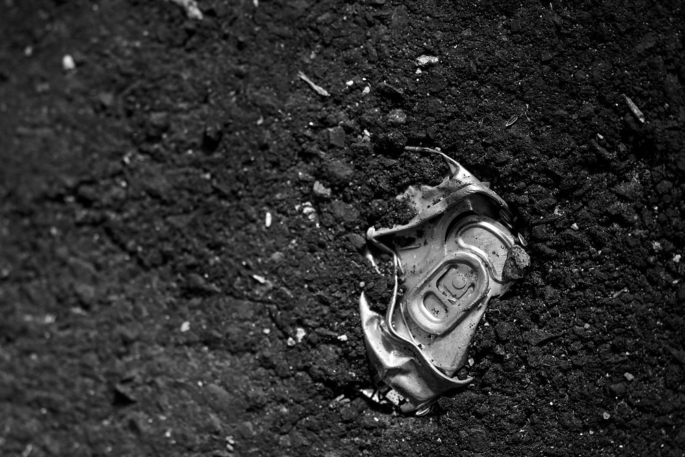 A black and white photograph of a soda can buried in black tar