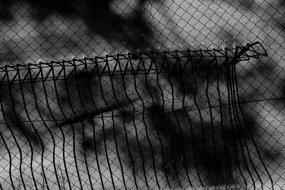 The shadow of a scrap fence leaning on construction mesh in black and white