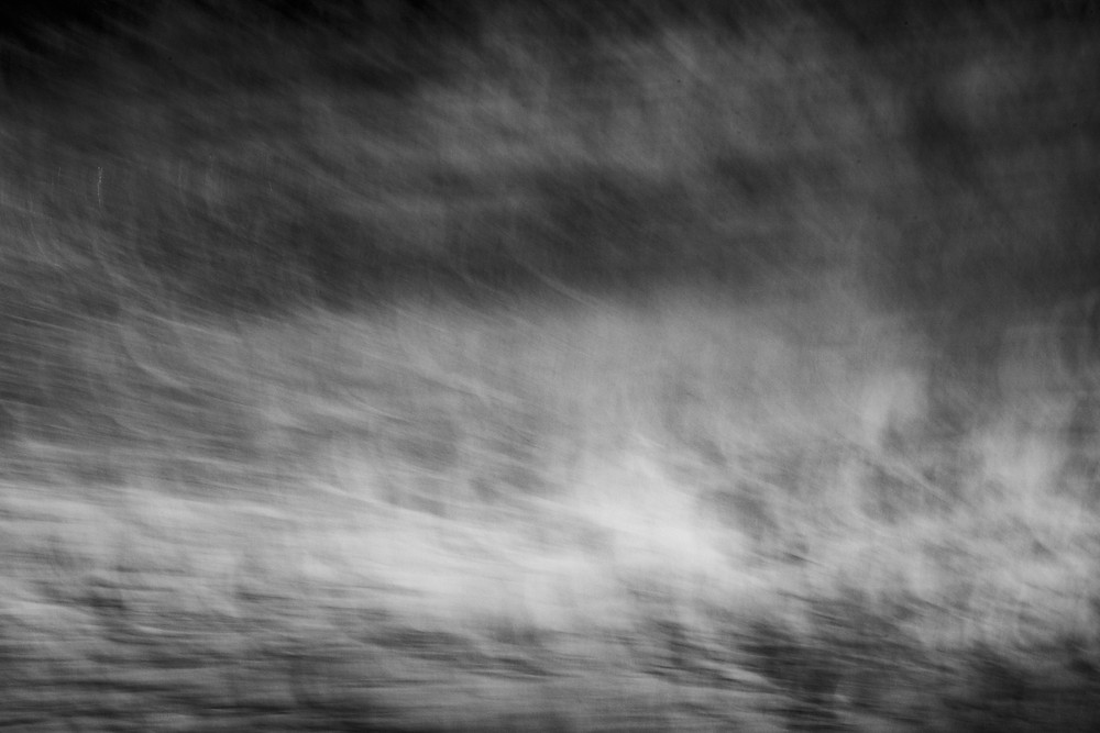 An abstract photograph of the ocean in black and white made with a long exposure technique.