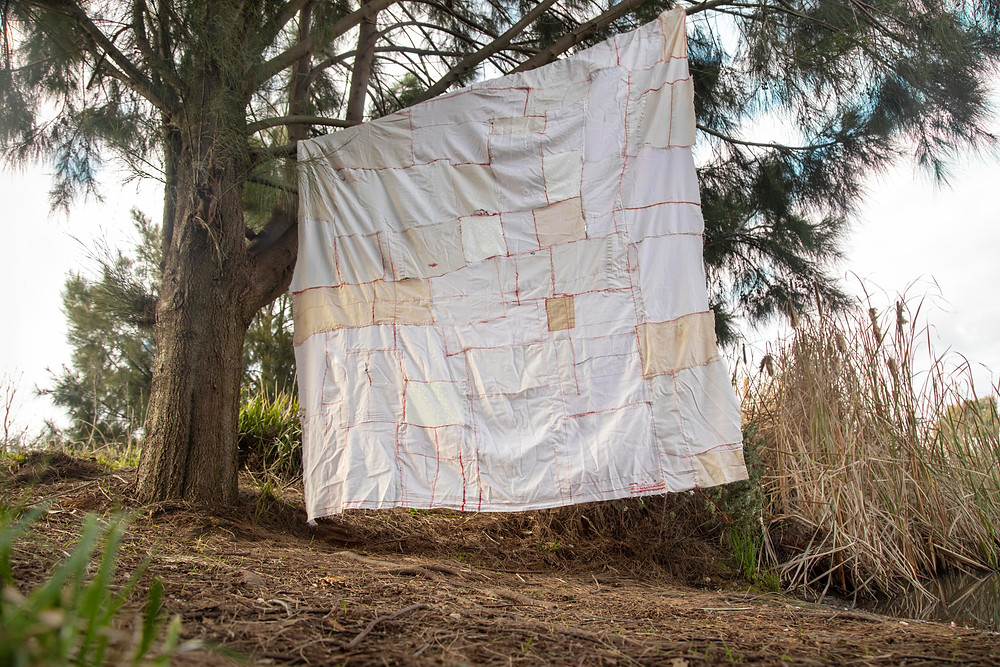 A textile artwork by Megan Kennedy hangs from a pine tree