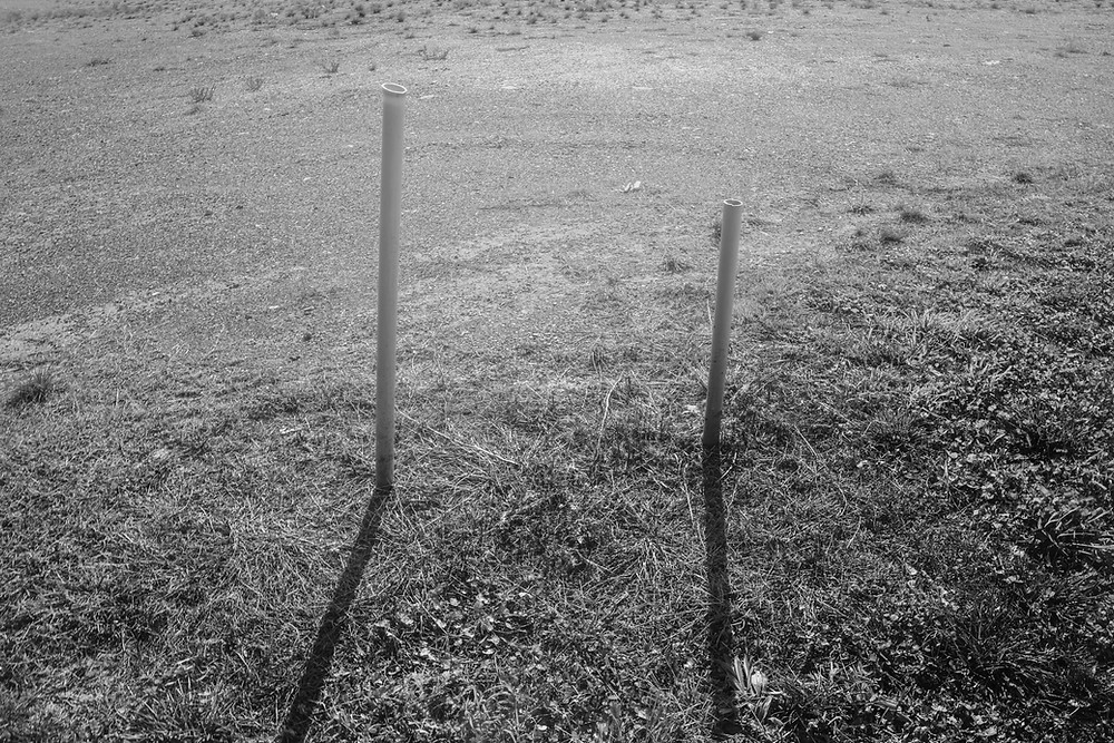 A black and white landscape depicting two short pipes puncturing the earth. Taken by Megan Kennedy