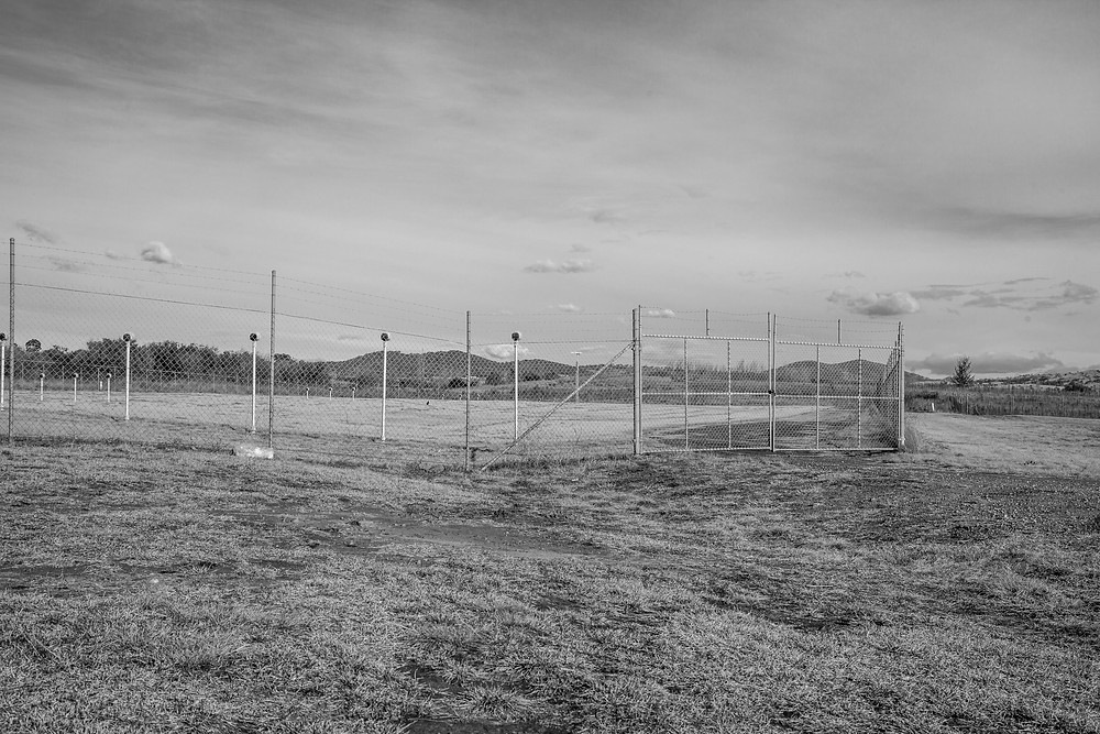 Canberra Airport approach lights behind a fence in black and white by Megan Kennedy
