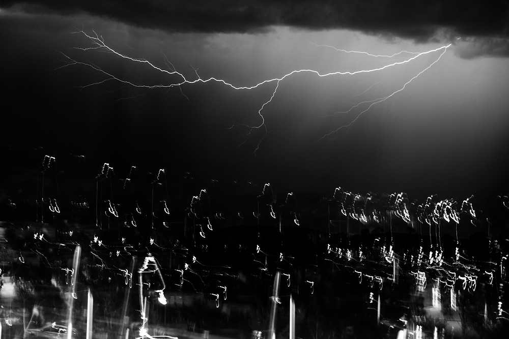 black and white photograph of lightning in Canberra, Australia with blurred lights in the foreground