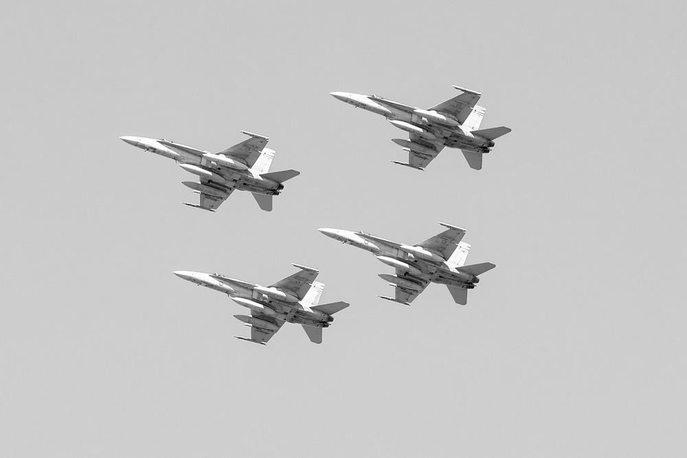 A black and white photograph of four RAAF fighters flying in formation