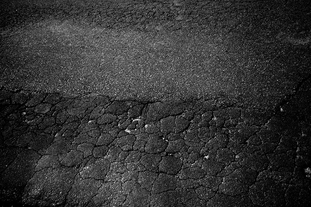 an example of crocodile cracking in asphalt roadside black and white photography