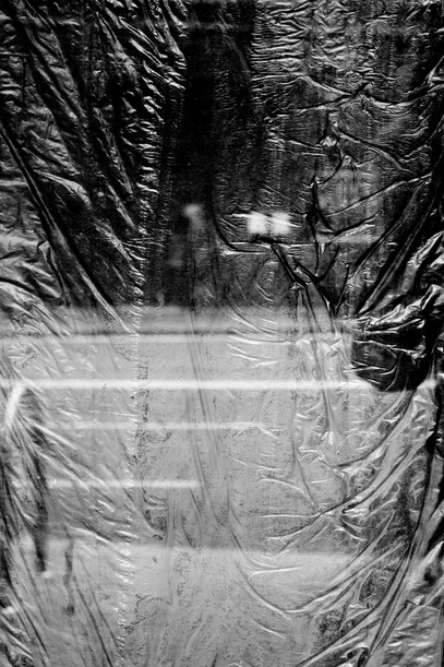 black and white window masked off with black garbage bags reflects a Sydney street