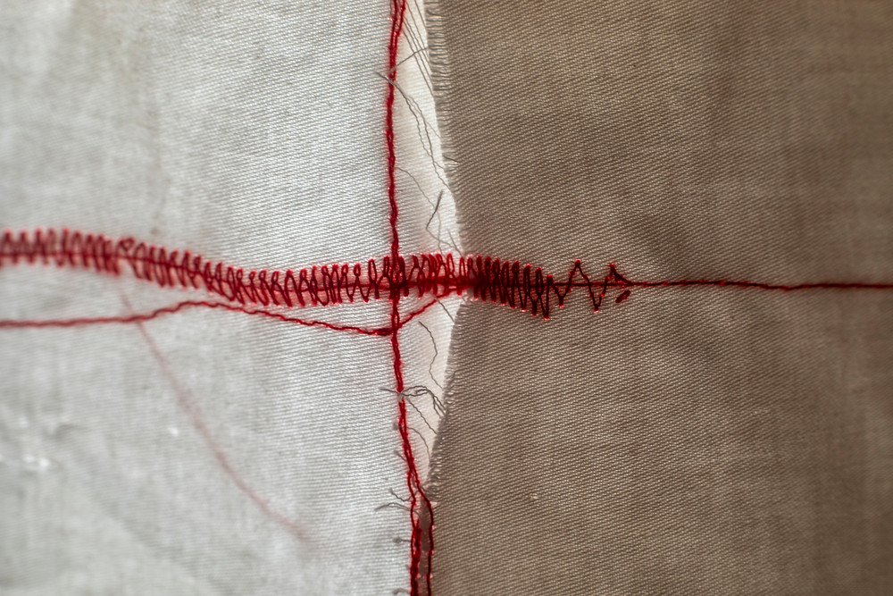Details of red thread and coffee-dyed fabric in a textile collage representing the materiality of sleep and chronic illness by Megan Kennedy
