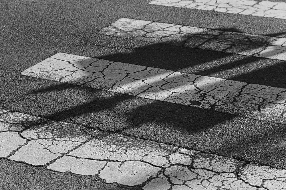 A photograph of a zebra crossing with the shadow of a traffic light by Megan Kennedy