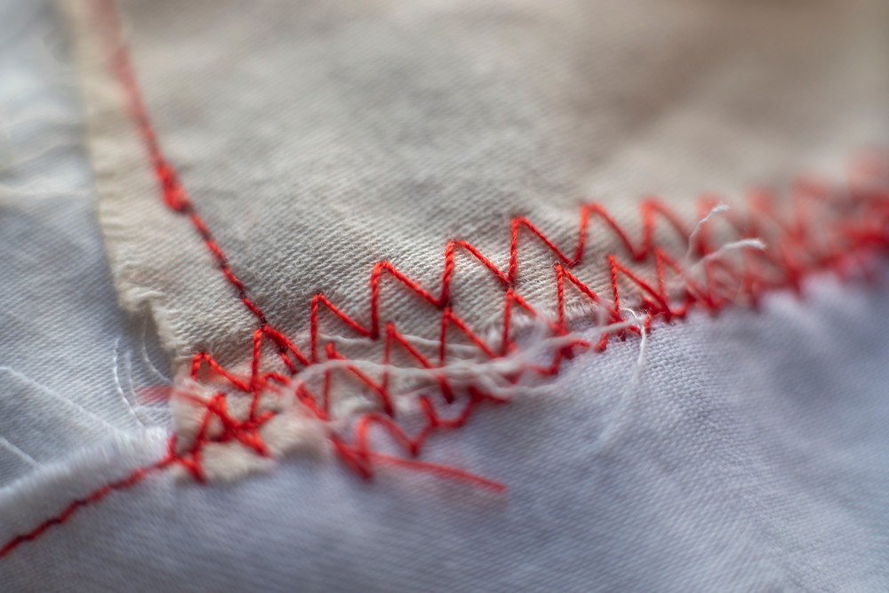 A detailed photograph of a zig-zag stitch binding a textile artwork about sleep by Megan Kennedy