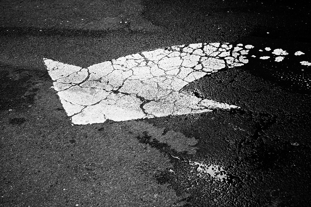A white traffic arrow on a road black and white photograph