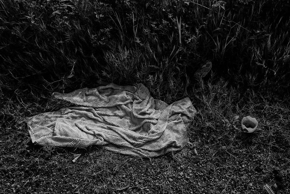 A black and white photograph of a towel and a plastic Easter egg discarded as trash