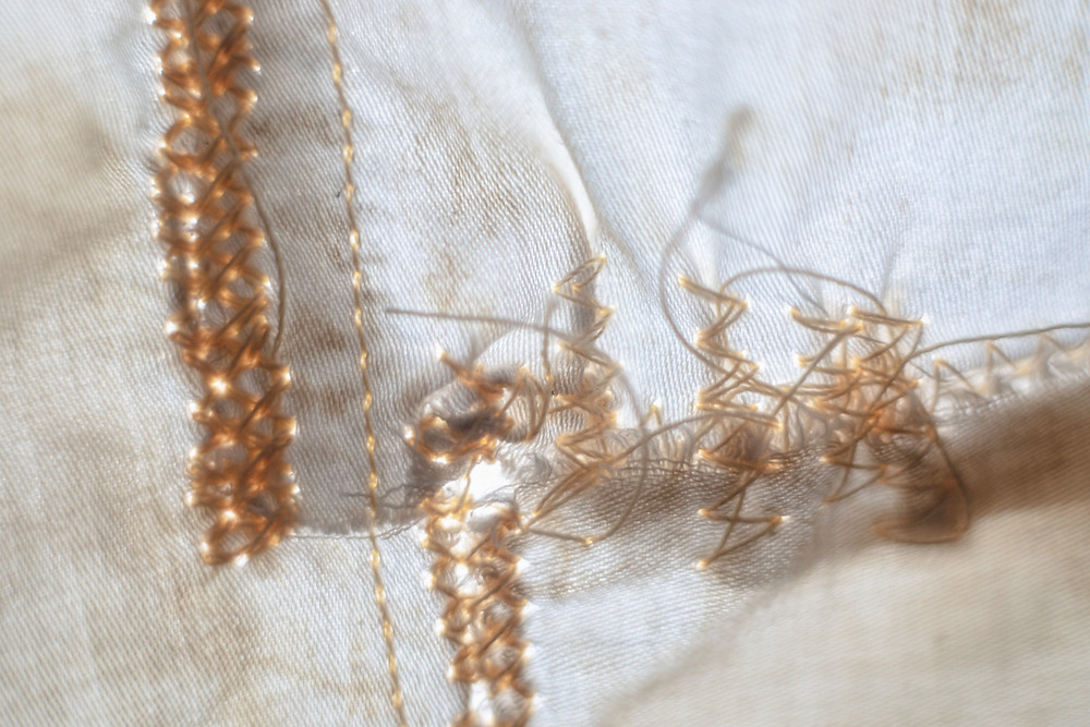 A photograph of white thread sewn into while sheet material. Photograph by Megan Kennedy