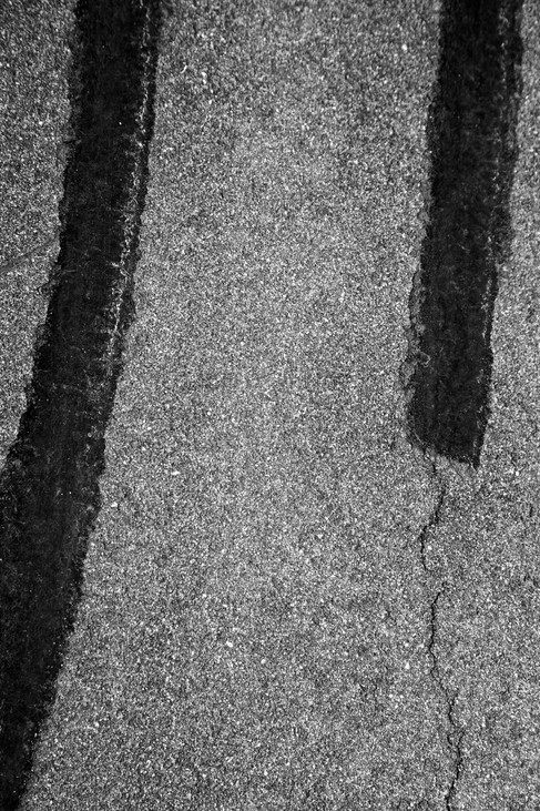 Black and white photograph of tar on a roadway
