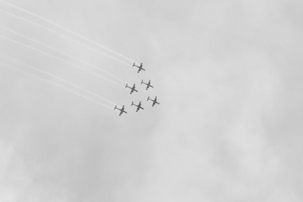 Six RAAF PC-21 aircraft fly in wedge formation as the Roulettes