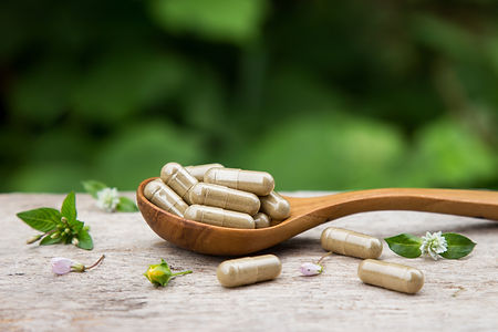 Pile of herbal capsules on wooden spoon