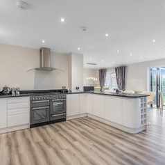 kitchen with white units and wood flooring