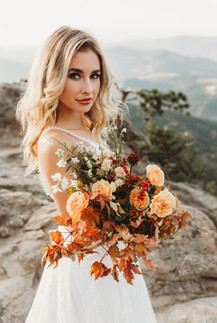 Beautiful bride on a mountainside during a mountain elopement in Colorado. Rocky Mountain elopement done by Christina J Photography. Arizona Photographer and Colorado photographer.